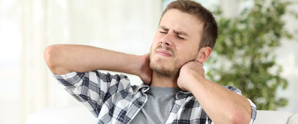 Man suffering neck pain sitting on a sofa in the living room at home